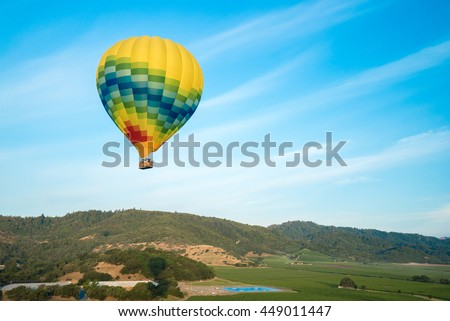 Multicolored hot air balloon floats in blue sunny sky over Norther California vineyards