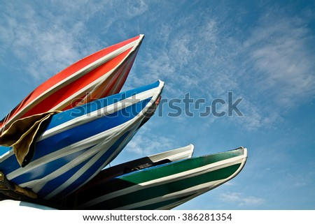 Multicolored kayaks against the blue sky