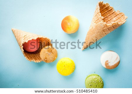 Multicolored macaroon cookies with ice cream cones on a blue background, top view, copy space