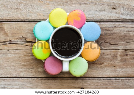Multicolored macaroon different lie in the saucer with coffee with the top view on the old wooden table - stock photo