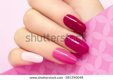 Multicolored manicure with different shades of pink nail Polish on women's hand. - stock photo