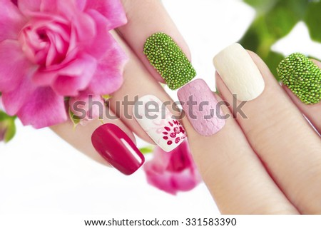 Multicolored manicure with flower pattern,green balls and a mesh pattern on the nails. - stock photo