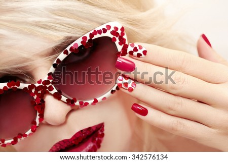 Multicolored manicure with red and white nail Polish decorated with rhinestones in the shape of hearts. - stock photo