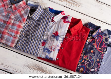 Multicolored men's shirts with different prints on the wooden background. - stock photo