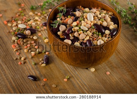Multicolored mixed beans, chickpeas  and lentils on a rustic  wooden table - stock photo