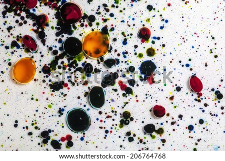 Multicolored paint dye splattered into shallow water creates a colorful and interesting pattern. - stock photo