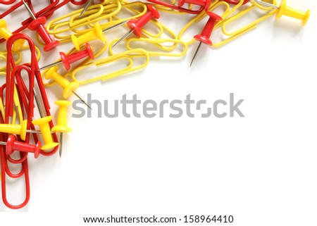 Multicolored paper clips and drawing pins on a white background - stock photo