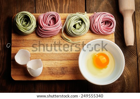 Multicolored pasta, egg yolk and daugh roller on wooden table top view - stock photo