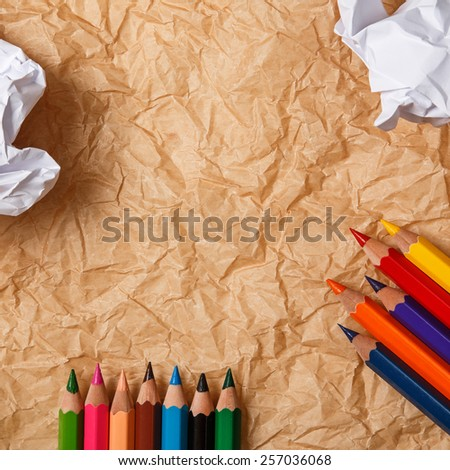 Multicolored pencils and crumpled paper - stock photo