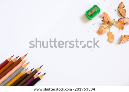 multicolored pencils growing row ,color sharpener and pencil shaves with shadow on white background ,Color pencils Background for business presentation - stock photo