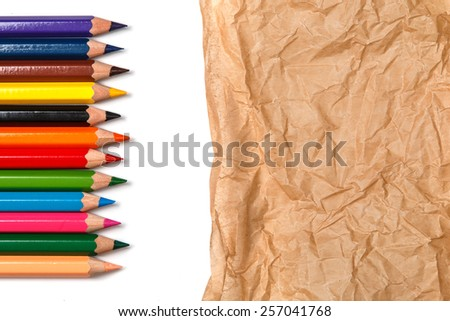 Multicolored pencils  over crumpled paper surface - stock photo