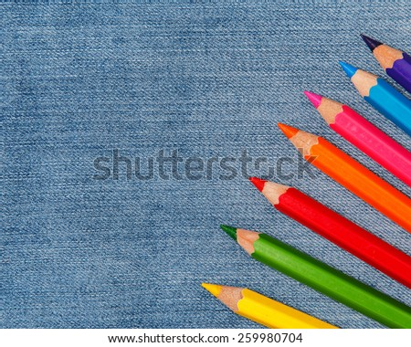Multicolored pencils over jeans surface - stock photo