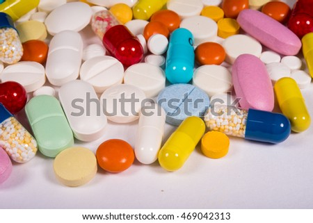 multicolored pills and tablets on a white background