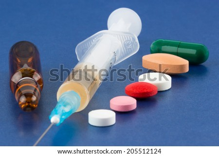 Multicolored pills, syringe with hypodermic needle, vial and ampoule on blue background - stock photo