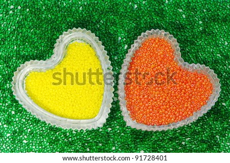 Multicolored plastic beads in heart-shaped crystal vases. - stock photo