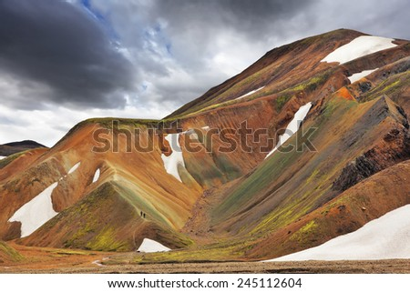 Multicolored rhyolite mountains with the remnants of last year's snow in July. The famous Valley Landmannalaugar in Iceland - stock photo