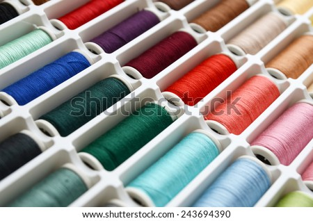 Multicolored sewing threads background closeup