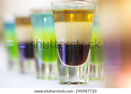 Multicolored shot alcoholic cocktails green blue white brown and gold colours standing in a line on table top in glasses closeup of drinks background, horizontal picture