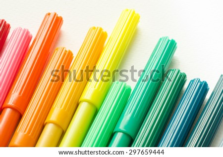 multicolored sketch pens on white paper background - stock photo