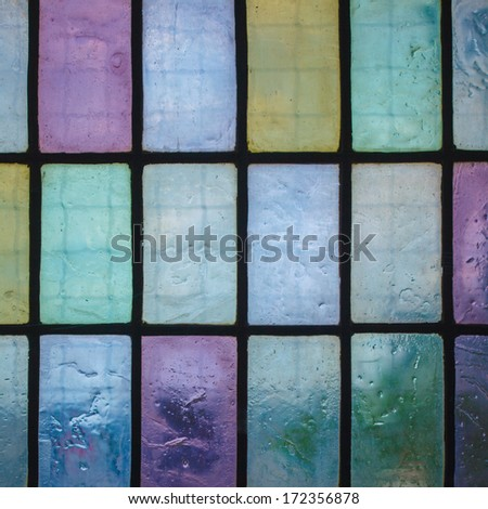 multicolored stained glass window with regular block pattern in hue of blue green violet, square format - stock photo