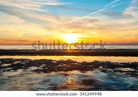 Multicolored summertime sunset on Baltic sea beach. Vibrant horizontal outdoors image - stock photo
