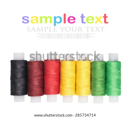 multicolored threads isolated on a white background. focus on bobbins, shallow depth of field. for example text and easily removed - stock photo