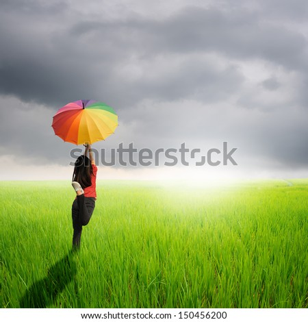 Multicolored umbrella woman jumping in green rice field and rainclouds