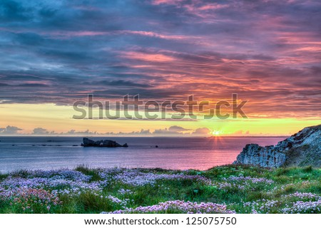 Multicolored yellow, orange, pink and blue sunset view of a rocky coastline in the Brittany region of France. This is a HDR image. / Sunset in Brittany, France - stock photo