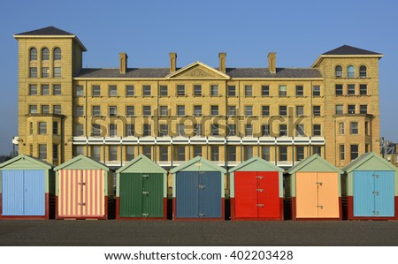 Multicoloured beach huts on seafront promenade at Brighton, East Sussex, England