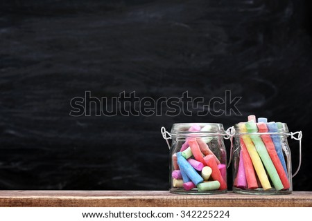 Multicoloured chalk in a jars on blackboard background - stock photo