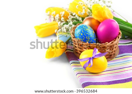 Multicoloured Easter eggs and tulips on napkin isolated on white - stock photo