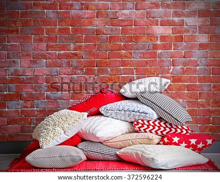 Multicoloured pillows on a brick wall background - stock photo