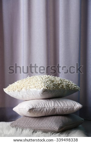Multicoloured pillows on a carpet in a room - stock photo