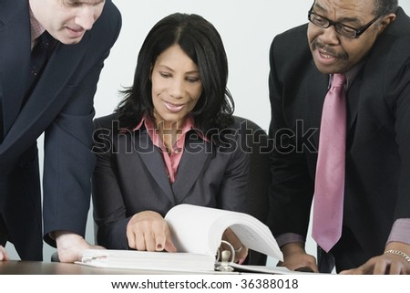 Multicultural business team reviewing document. - stock photo