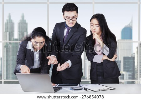 Multicultural business team standing in office while discussing with laptop on desk - stock photo
