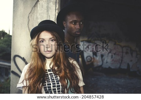 multicultural couple portrait in an urban place with graffiti - stock photo