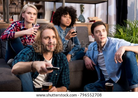 multicultural friends watching tv with alcohol at home