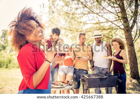 Multicultural group of friends grilling and having party in the backyard - Barbecue outdoors, cheerful people cooking meat and drinking wine - stock photo