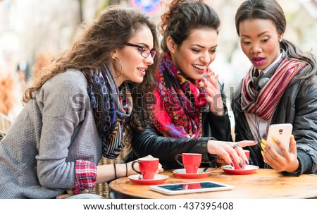 Multicultural group of women in cafe showing each other pictures on smart phone and chatting - stock photo