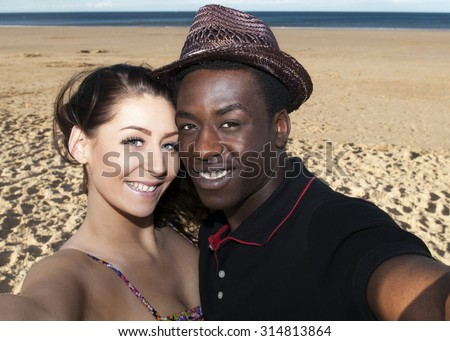 Multicultural young couple taking selfie smiling  in love  on beach  posing having fun - stock photo