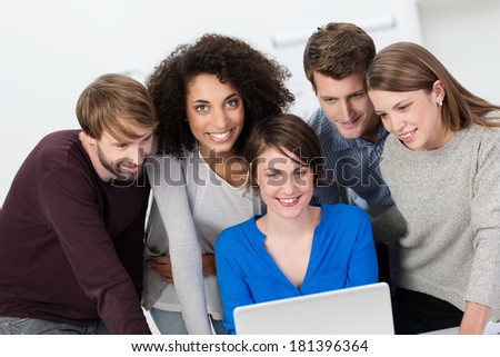 Multiethnic business team working in the office grouped around a laptop computer with an attractive African American woman looking up with a smile - stock photo