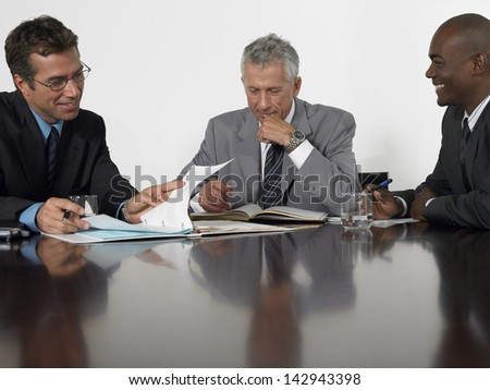 Multiethnic businessmen reading documents in conference room - stock photo
