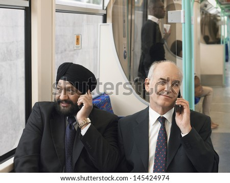 Multiethnic businessmen sitting in commuter train and using cellphones - stock photo