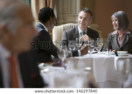 Multiethnic businesspeople sitting at restaurant table and talking - stock photo