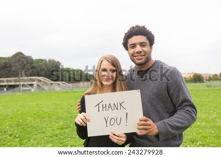 Multiethnic Couple Saying Tahnk You with a Board - stock photo