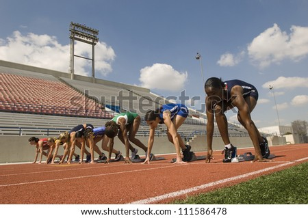 Multiethnic female athletes at starting line on race track - stock photo
