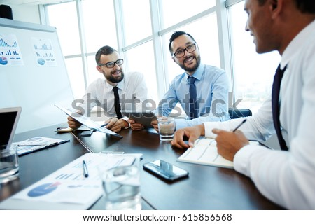 Multiethnic group of businessmen gathered in modern boardroom and discussing their joint project, one of them taking notes