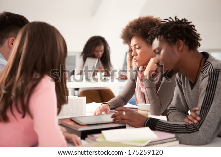 Multiethnic group of cheerful college students studying together. - stock photo