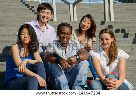 Multiethnic group of five university students sitting on steps of university smiling, metaphor for diversity and international friendship - stock photo