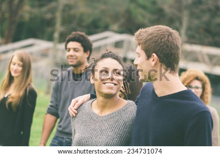 Multiethnic Group of Friends at Park. A caucasian Man with a Mixed-Race Woman are in foreground and some others in background. They seem to be happy - stock photo